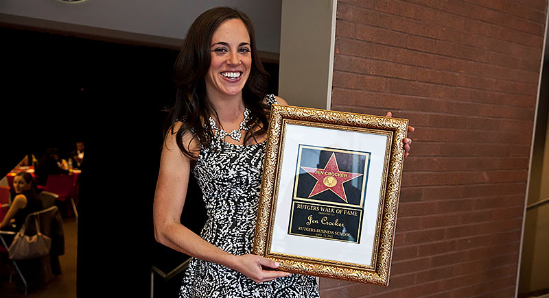 Jen Crocker holding a framed photo of here RBS Star in the Rutgers Walk of Fame