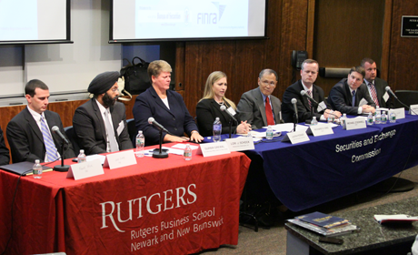Two tables of panelists speaking at the event