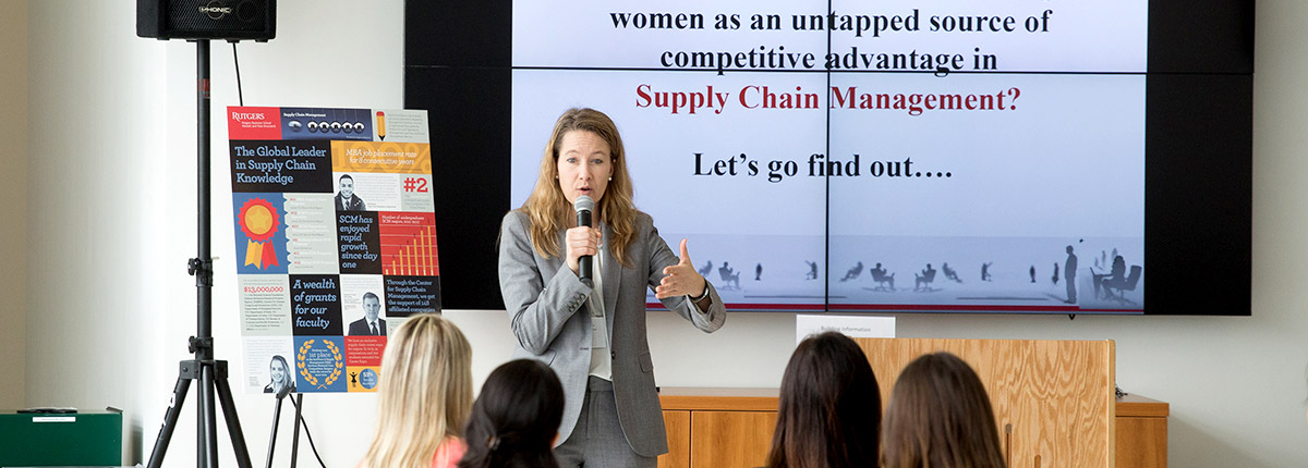 A professor presents a slideshow presentation about supply chain management and how women can be tapped into as a source for competitive advantage.