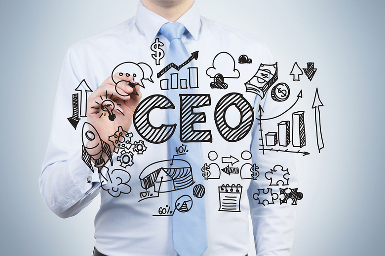 A person writing with black marker on the screen the word CEO with other drawings surrounding it
