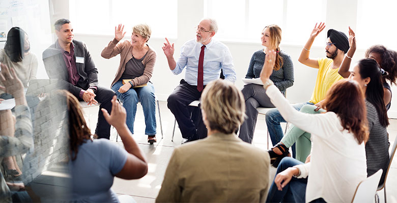 Many different types of people sit together in a circle with some raising there hands in participation