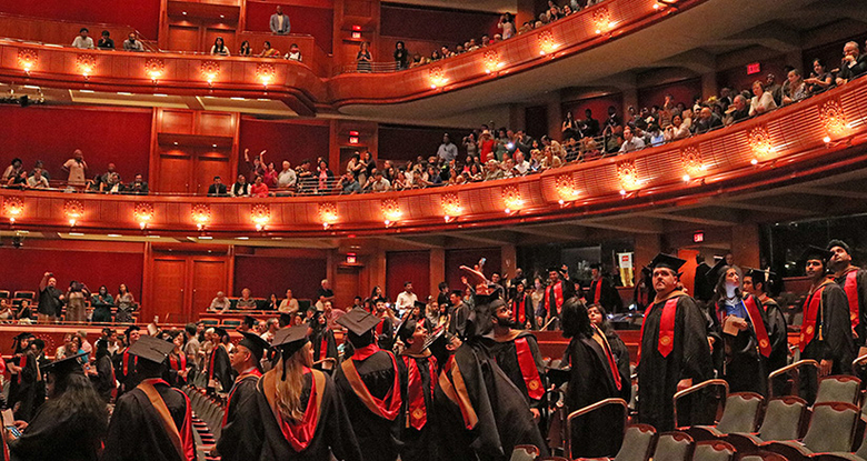 Graduating Rutgers graduate students scan the crowd for family and friends as they file into the New Jersey Performing Arts Center.