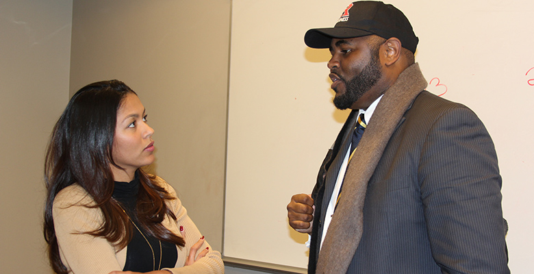 Derrick Griggs, chief operations officer at the Affordable Housinal Alliance, speaks with a student after the panel discussion.