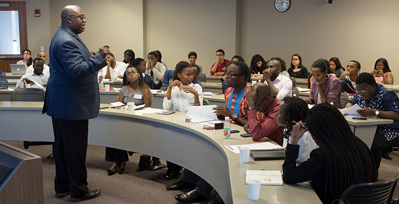 Professor Kevin Lyons during a session of the program that offered the high school students a chance to work alongside the Mandela Washington Fellows. In the Photo, Some of the fellows are seated in the first row of seats.