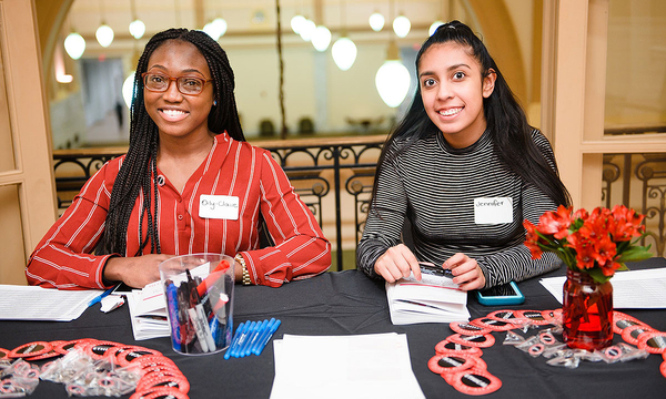 Two Interns help out at a table at an IEL event