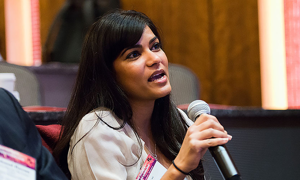 A woman with long black hair holding a microphone speaks at a past symposium