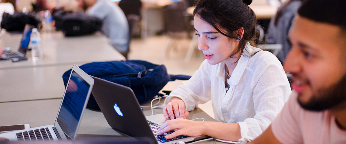 female student typing on laptop