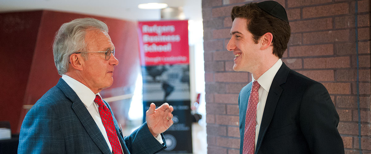 Alumni speaks with professor at RBS event.
