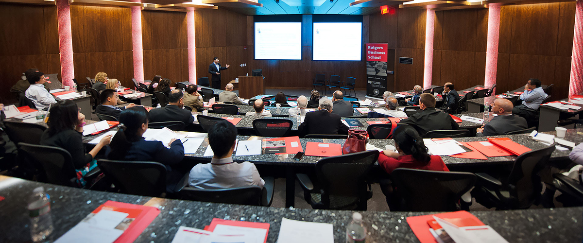 Wide angle shot of audience viewing presentation on projection screens