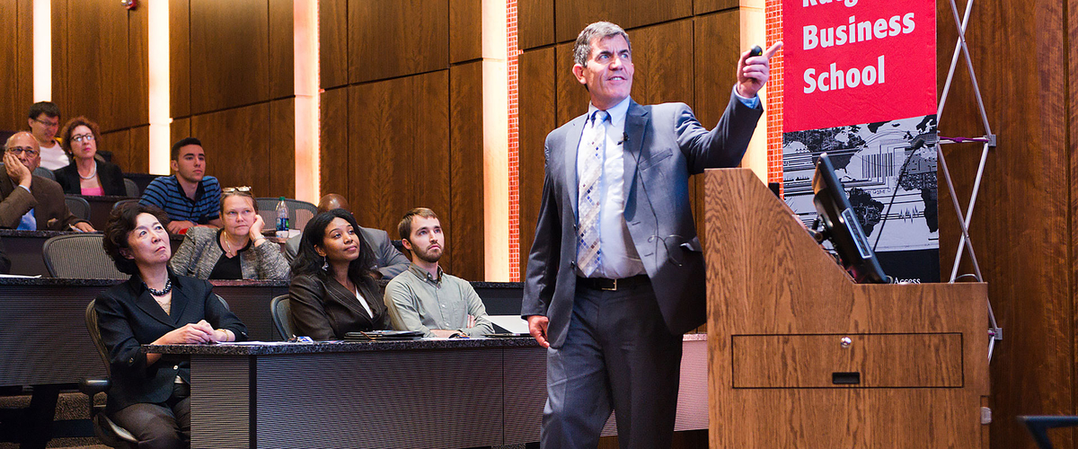 Ted Baker presents to an audience within Bove auditorium on the Newark campus
