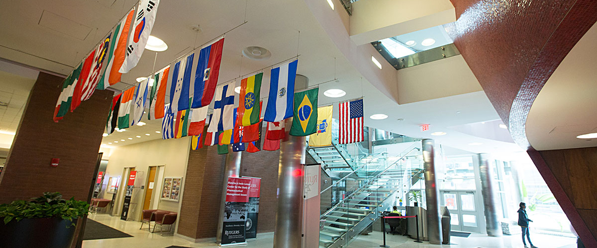 Indoor view of 1 Washington park's lobby with flags from many different countries displayed from the ceiling.