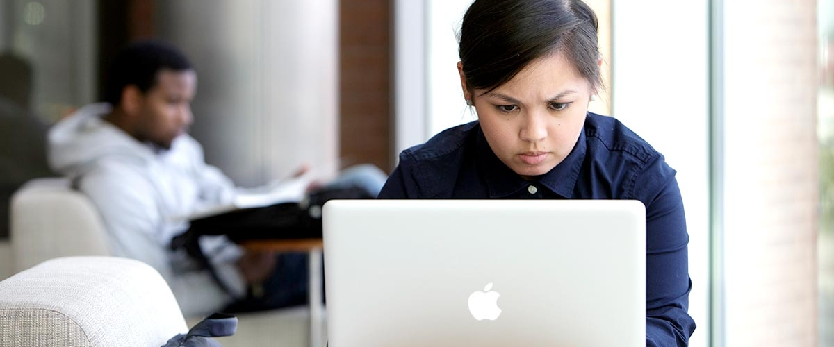 A student focuses on her laptop in the campus lobby