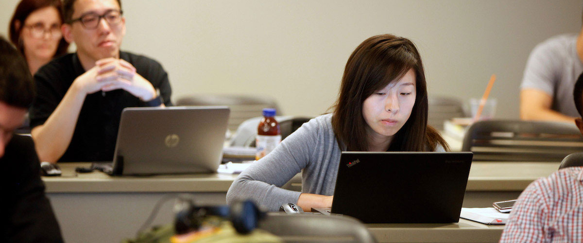A female student's face glows in the light from her laptop as she sits in class