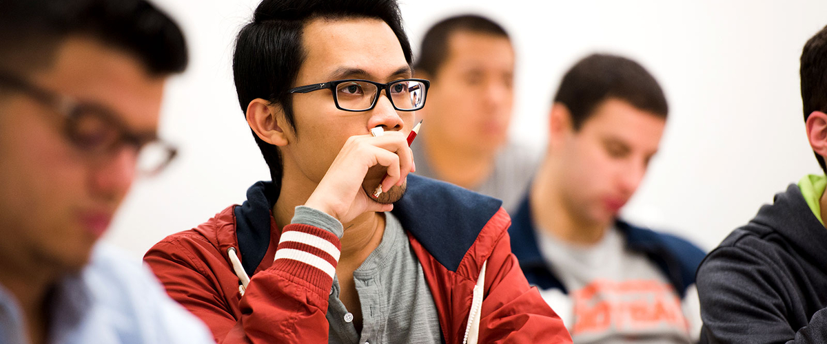 Students in class. One male student looks intently forward
