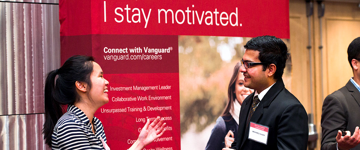 Students smiling at a career fair in front of the Vanguard Careers booth.