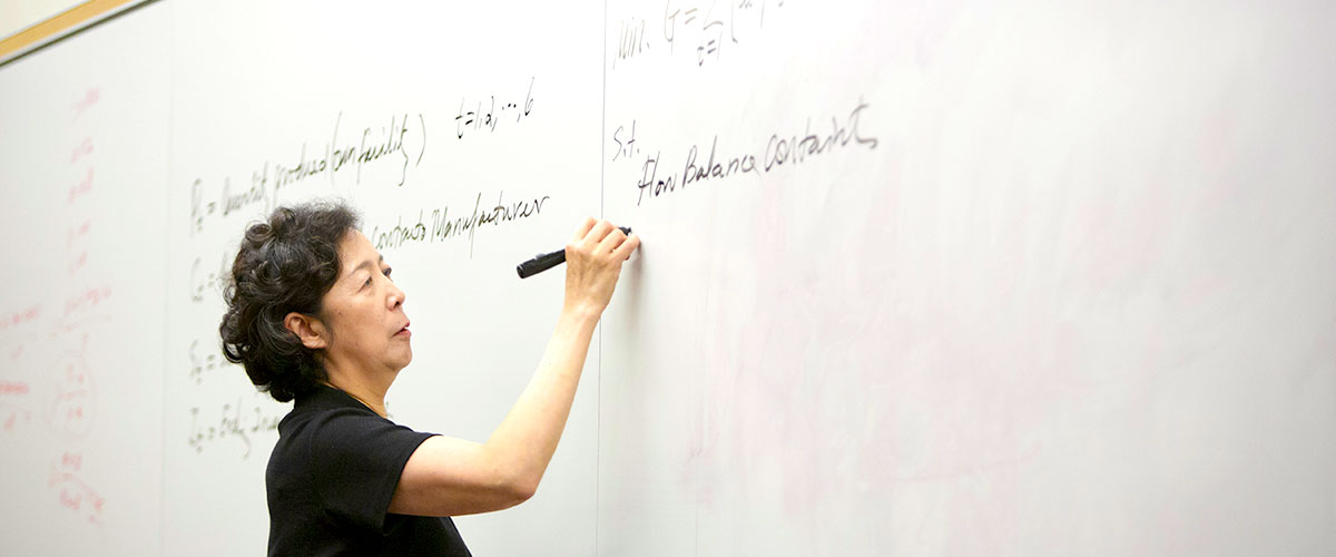 Dean Lei writes on a whiteboard with a black marker during class