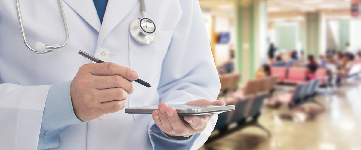 A doctor holds a tablet and stylus while wearing a stethoscope around their neck in a waiting room.