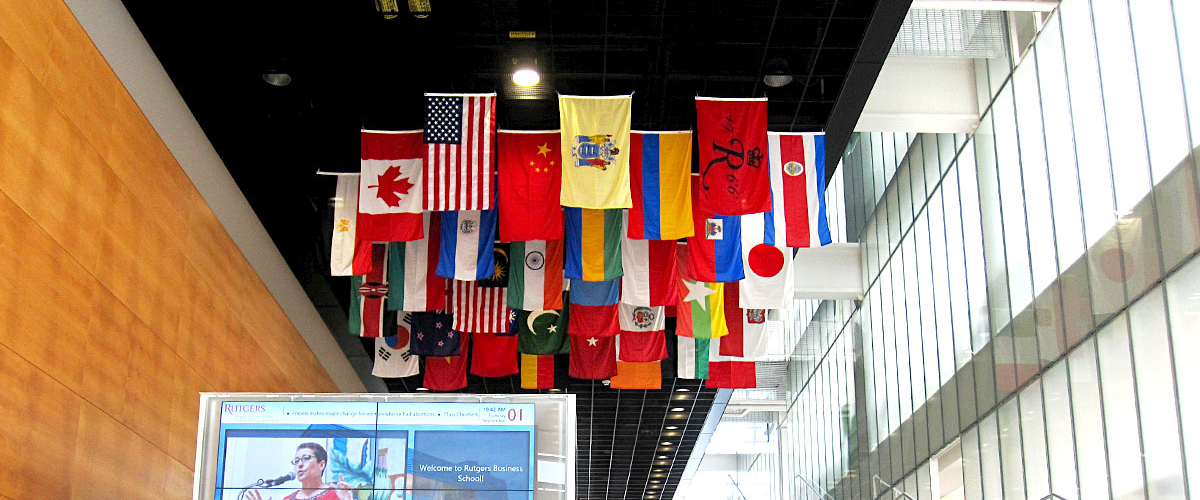 Inside shot of the staircase at 100 Rock with various countries' flags haning from the ceiling.