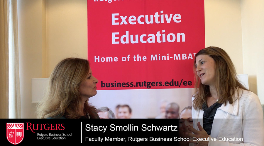 Screenshot of video where Stacy Smollin Schwartz is talking to Jackie Scott in front of an Executive Education banner