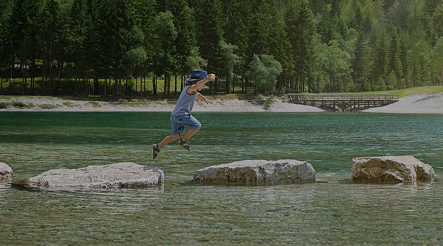 Child hopping across rocks in a stream.